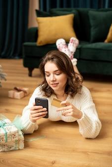 Ragazza sorridente con smartphone e carta di credito vicino all'albero di natale. acquisti online per il nuovo anno. sta comprando regali