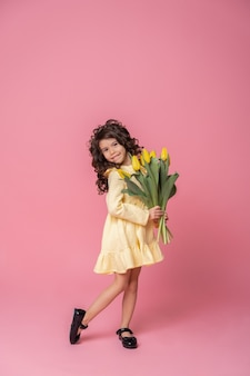 Ragazza sorridente in abito giallo su sfondo rosa studio. allegro bambino felice con bouquet di fiori di tulipani.