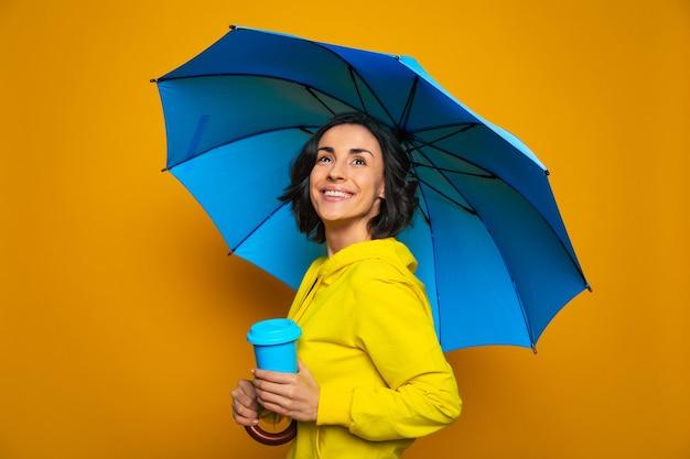 Ragazza sorridente in una giacca gialla sotto un ombrello, con una tazza termica blu nella mano sinistra, alzando lo sguardo speranzoso, godendosi la pioggia.