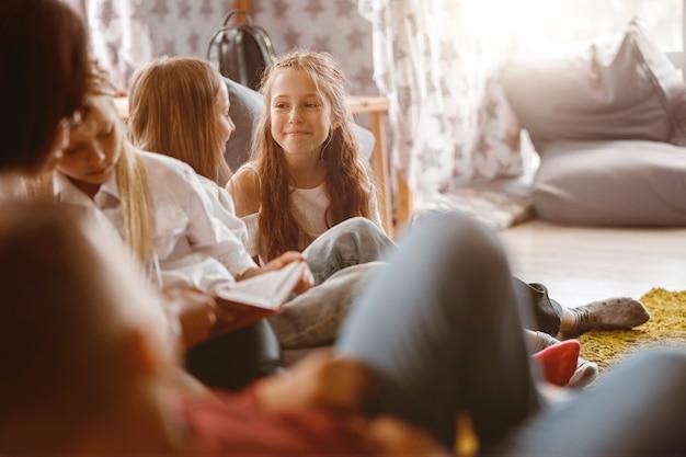Ragazze sorridenti che chiacchierano durante una lezione a scuola