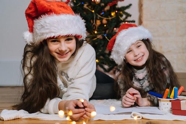 Ragazze sorridenti in cappello della santa che scrive la lettera per i regali a babbo natale.