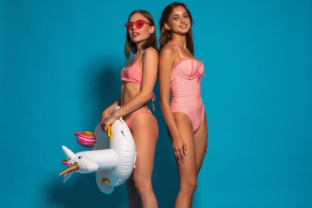 Ragazze sorridenti in costume da bagno con anello di gomma unicorno sulla parete blu