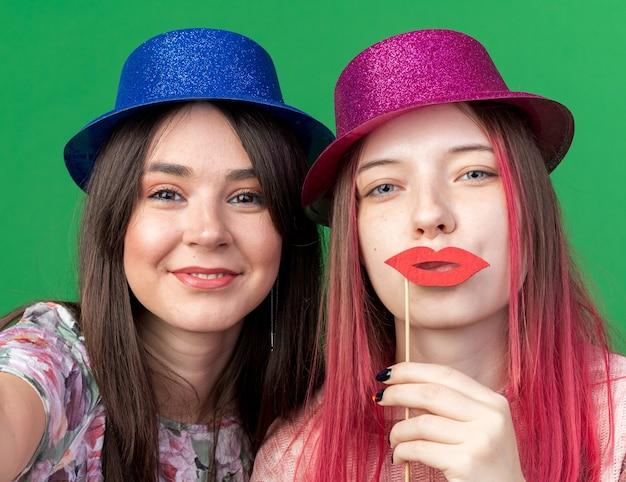 Ragazze sorridenti che indossano un cappello da festa con in mano la macchina fotografica e baffi finti sul bastone