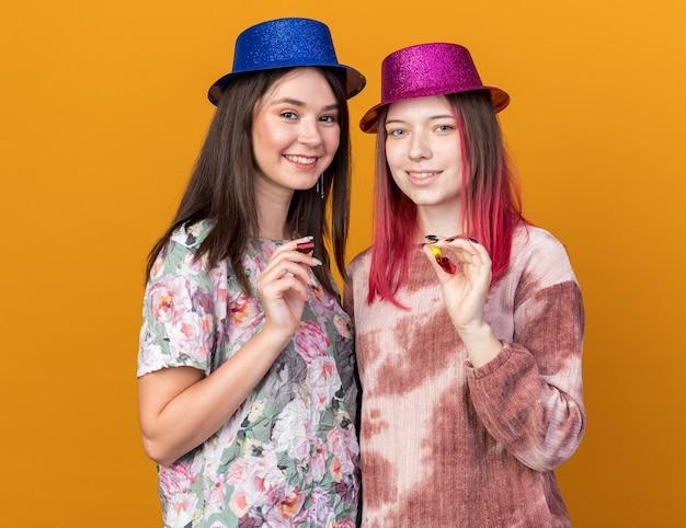 Ragazze sorridenti che indossano il cappello da festa che tengono il fischio della festa isolato sulla parete arancione