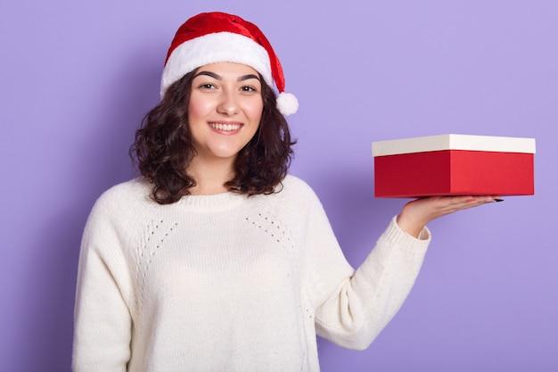 Sorridente bella ragazza in possesso di scatola rossa e bianca sul palmo della mano, guardando direttamente la fotocamera, preparando per il nuovo anno
