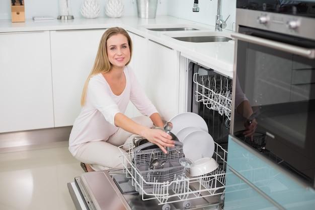 Modello splendido sorridente che si inginocchia dietro la lavastoviglie