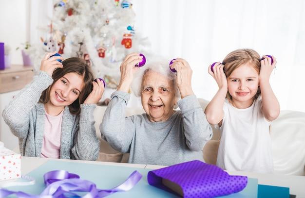 Nipoti sorridenti che tengono le palle decorative come gli occhi con la nonna a natale