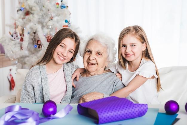 Sorridente nipoti con la nonna seduti insieme a natale