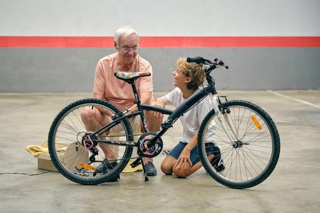 Nonno sorridente che parla con il nipote mentre ripara la bicicletta