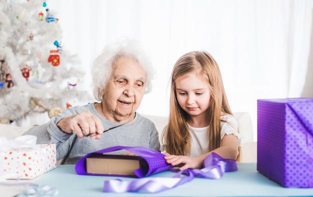 Nonna sorridente con la nipote che decora i regali a natale