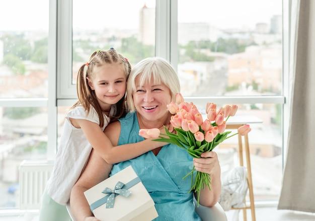 Nonna sorridente con regali da nipote