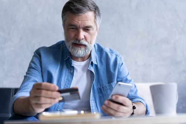 Sorridente uomo anni '50 dai capelli grigi paga le bollette online utilizzando un moderno gadget per smartphone e una carta di credito. il cliente maturo felice della banca effettua l'acquisto di pagamento via internet sul cellulare da casa. concetto di tecnologia.