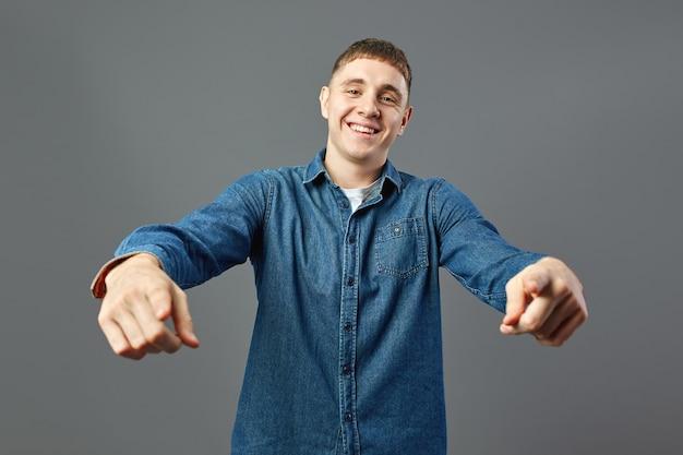 Ragazzo sorridente vestito con una camicia di jeans punta con le mani in avanti in studio sullo sfondo grigio.
