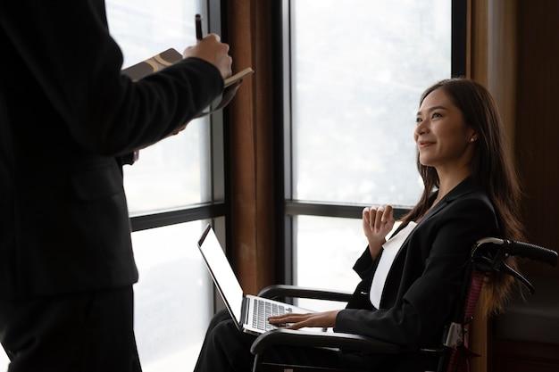 Sorridente giovane donna handicappata che lavora con il suo collega in ufficio.