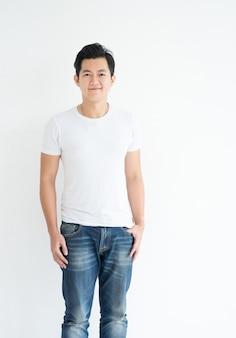 Uomo asiatico bello sorridente in maglietta bianca casuale con i jeans che esaminano colpo dello studio della macchina fotografica isolato su fondo bianco