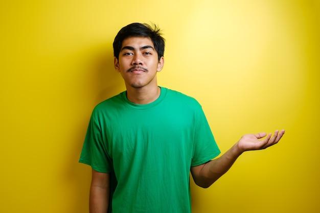 Sorridente bell'uomo asiatico che punta il dito verso la mano aperta vuota isolata su sfondo giallo