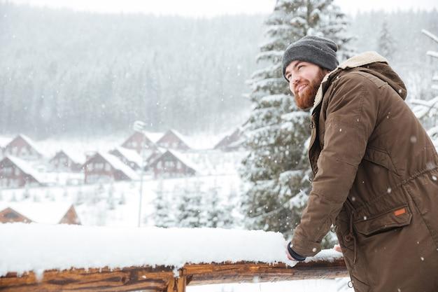 Sorridente bell'uomo barbuto in piedi e godendo il tempo nevoso nella località invernale