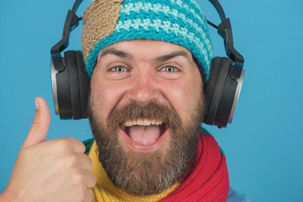 L'uomo barbuto bello sorridente con la barba in cappello e sciarpa in cuffia godendo musik, mostra il gesto ok. il macho barbuto in cuffia ascolta musica. concetto di svago.