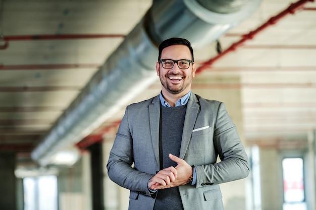 Sorridente bell'uomo d'affari caucasico in tuta è felice di presentare il proprio progetto mentre si trovava nell'edificio in costruzione.