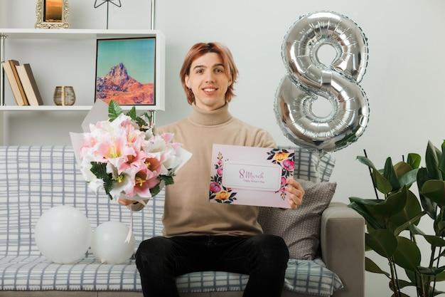 Sorridente bel ragazzo il giorno delle donne felici che tiene bouquet con biglietto di auguri seduto sul divano in soggiorno