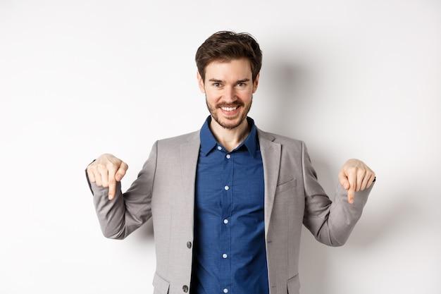 Sorridente bell'uomo in giacca e cravatta che punta le dita verso il basso, mostrando un buon affare, guarda qui gesto, in piedi su sfondo bianco.