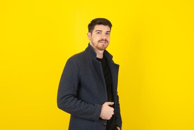 Uomo bello sorridente che guarda l'obbiettivo su un giallo.