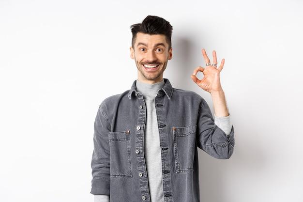 Uomo bello sorridente che mostra segno ok, come un buon prodotto, raccomandando pubblicità, in piedi soddisfatto su sfondo bianco.