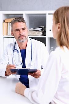 Il medico maturo bello sorridente comunica con il paziente