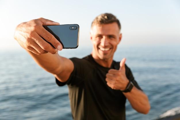 Sportivo senza camicia bello sorridente che prende un selfie