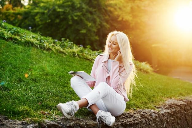 Musica di rilassamento d'ascolto della donna bella sorridente nelle cuffie con il suo telefono cellulare o compressa al parco. lo studente ascolta una lezione online e si prepara per gli esami.