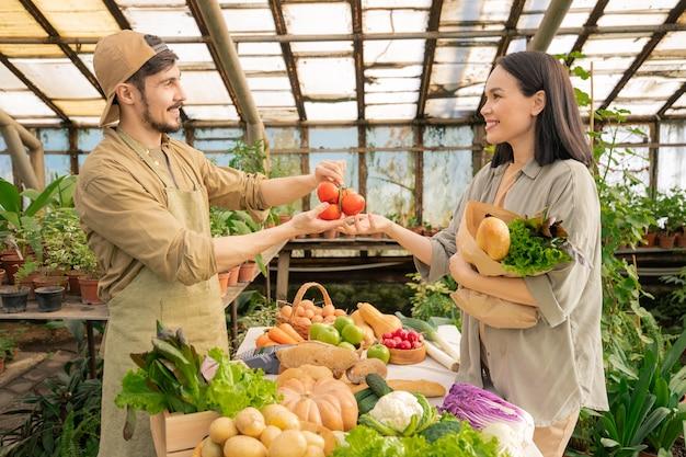 Sorridente bel giovane barbuto agricoltore in grembiule e berretto che vende verdure mature alla donna asiatica nella casa della drogheria