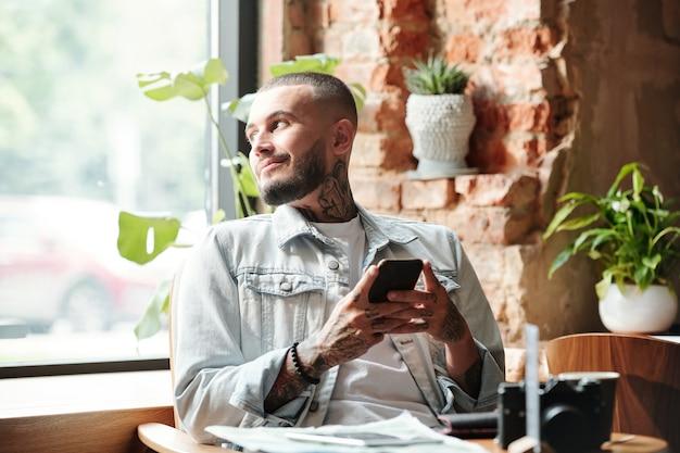 Sorridente bel giovane in giacca di jeans seduto al tavolo e messaggio di testo in attesa di un amico nella caffetteria