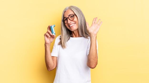Sorridere allegramente e allegramente, agitare la mano, darti il benvenuto e salutarti o salutarti. concetto di asma