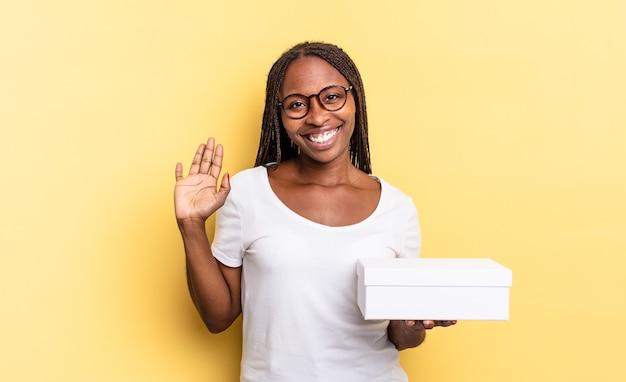 Sorridere allegramente e allegramente, agitando la mano, accogliendoti e salutandoti, o salutandoti e tenendo in mano una scatola vuota
