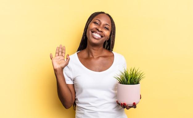 Sorridere allegramente e allegramente, agitare la mano, darti il benvenuto e salutarti, o salutarti tenendo un vaso per piante