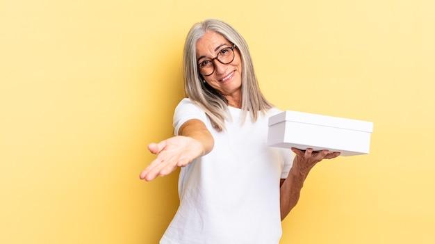 Sorridere felicemente con uno sguardo amichevole, fiducioso e positivo, offrendo e mostrando un oggetto o un concetto e tenendo in mano una scatola bianca