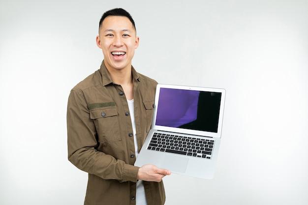 Computer portatile asiatico felice sorridente della tenuta dell'uomo con il modello in sue mani su un fondo bianco dello studio