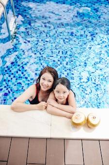 Sorridendo felice donna asiatica e la sua piccola figlia in piedi sul bordo della piscina, bevendo acqua di noce di cocco e guardando in alto