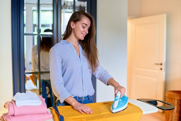 Sorridente felice bella carina soddisfatta moderna giovane donna adulta che stira i vestiti lavati sull'asse da stiro a casa. faccende domestiche