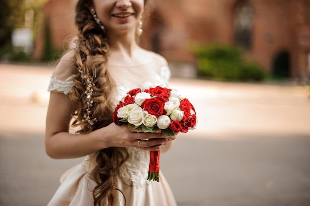 Sorridente sposa felice in un abito da sposa con un'acconciatura a treccia che tiene un mazzo di rose rosse e bianche