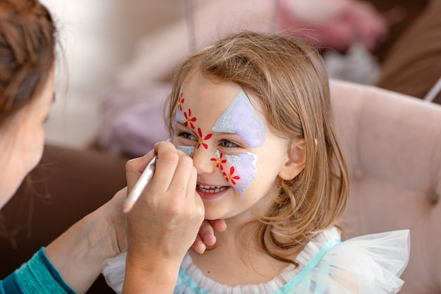Sorridente bambino felice con face art aqua grimm per il compleanno o la festa di halloween face art painting