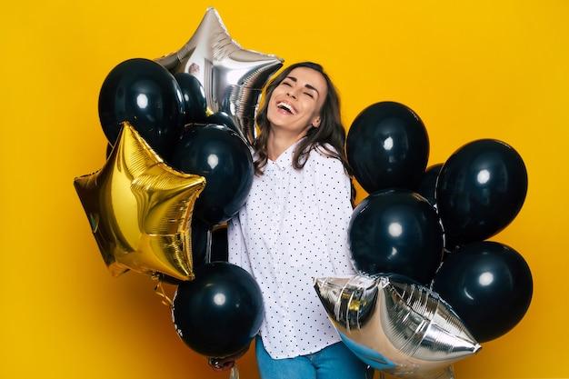 Sorridente felice ragazza carina eccitata che tiene in mano molti palloncini neri sta posando sullo sfondo giallo mentre fa shopping il black friday