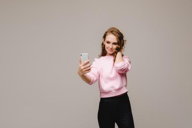 Una ragazza sorridente felice in una camicetta rosa prende un selfie su uno smartphone su uno sfondo grigio