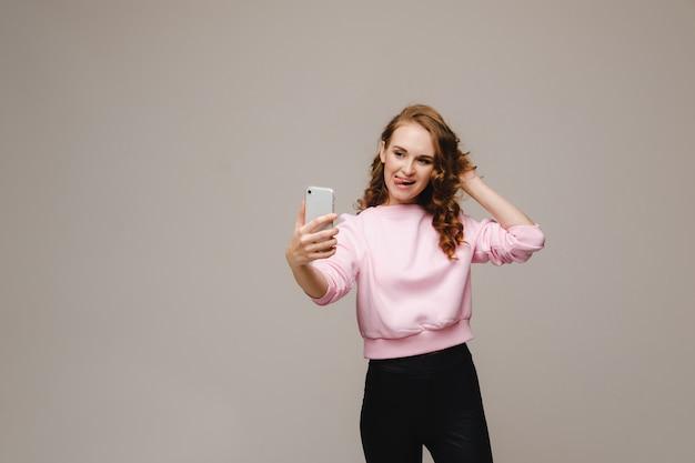 Una ragazza sorridente felice in una camicetta rosa prende un selfie su uno smartphone su un grigio.