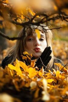 Ritratto felice sorridente della ragazza con le foglie di autunno. giovane donna tra foglie autunnali dorate. momento romantico in una luce calda. parco con foglie gialle e atmosfera autunnale.