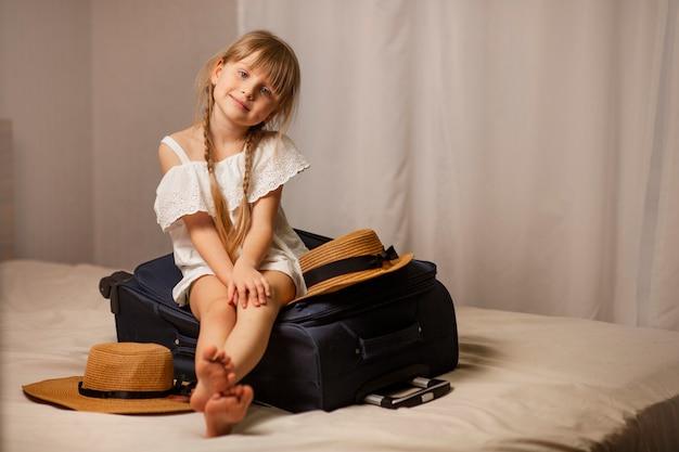 Sorridente ragazza felice che si siede su una valigia di borsa da viaggio bagagli in una sistemazione in camera d'albergo al trasferimento dell'hotel e viaggio al mare riposano cappelli di paglia si trovano nelle vicinanze