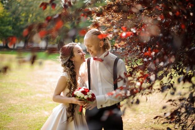 Sorridente e felice coppia sposata che cammina in un parco verde con prato e bellissimi alberi