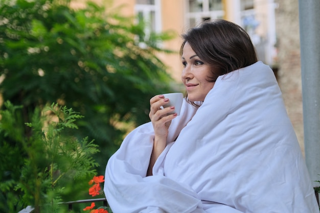 La donna di mezza età felice sorridente con la tazza di caffè si è vestita in coperta