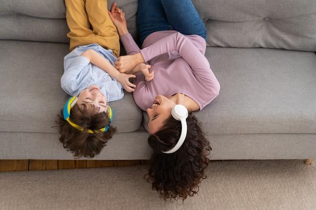 Sorridendo felice madre e bambino sdraiato sul divano a casa ridendo e solleticandosi a vicenda, ascoltando musica