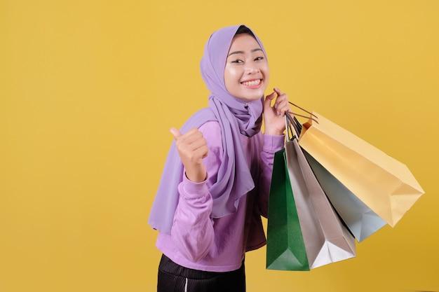 Sorridente ragazza carina felice utilizzando la carta di credito per sprecare soldi nel centro commerciale, con in mano borse della spesa, comprare regali o regali, concedersi una giornata, ridendo allegramente
